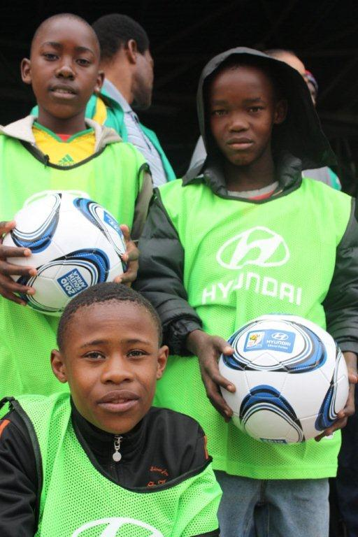 Children from local township schools are presented with SOS Africa / Hyundai 2010 World Cup Football Project footballs