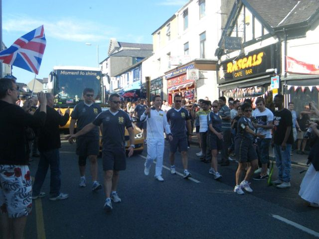 Matthew carrying the Olympic Flame through Bangor for SOS Africa